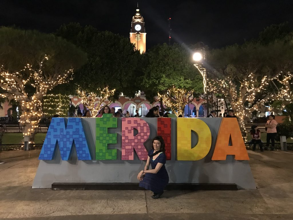 Heather in front of the Merida sign with Christmas lights in the background.