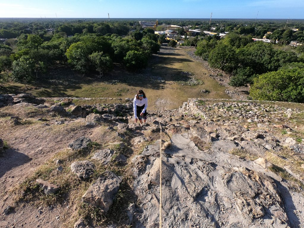 Heather climbing Kinich Kakmo with Izamal's Convento in the background below.