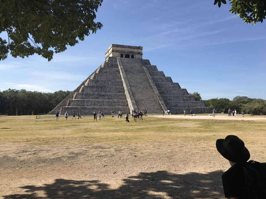 Pier looking at pyramid from shade of tree. Chichen Itza, Mexico.