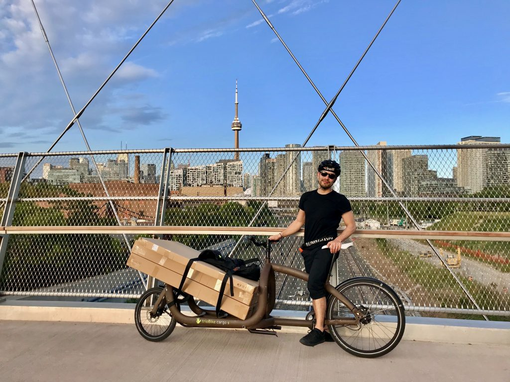 Triobike Cargo with load on bridge in front of CN Tower, Toronto.
