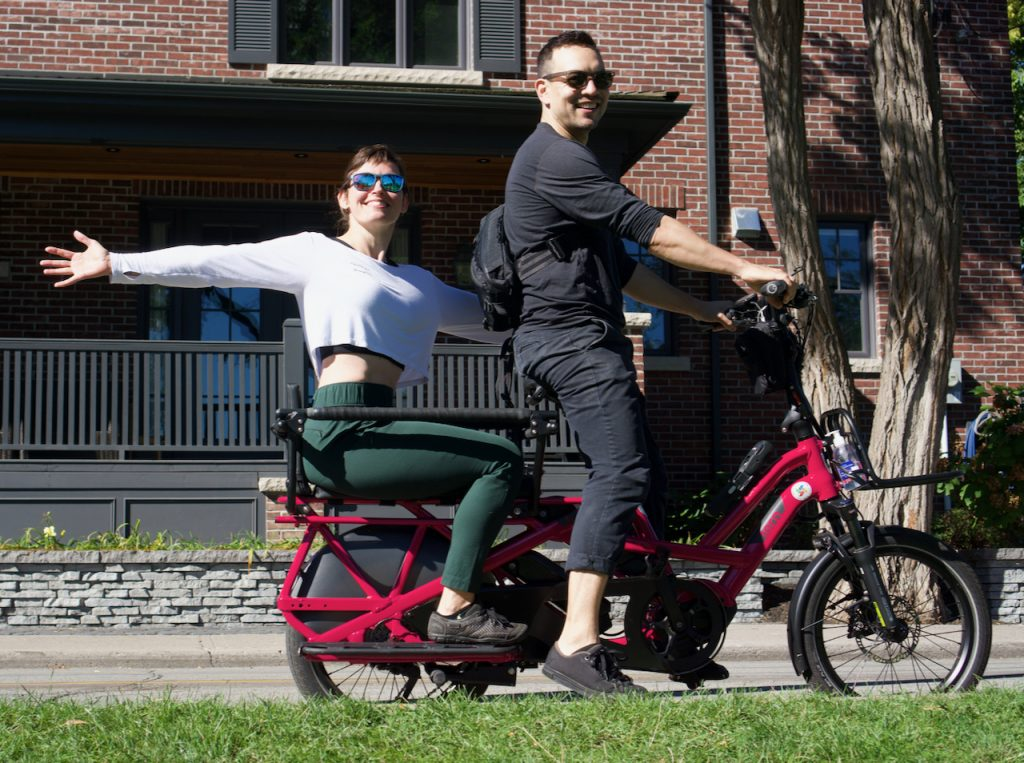 Two adults on a Tern GSD electric longtail cargo bike.