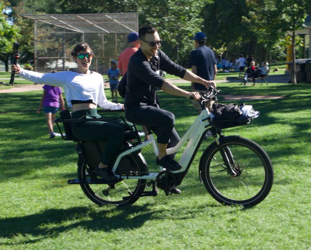 Two adults riding a Riese & Muller Multicharger electric cargo bike.